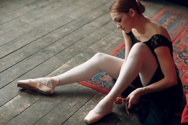 バレリーナの女性。プロの服、トウシューズ、黒のチュチュに身を包んだ若い美しい女性バレエダンサー。