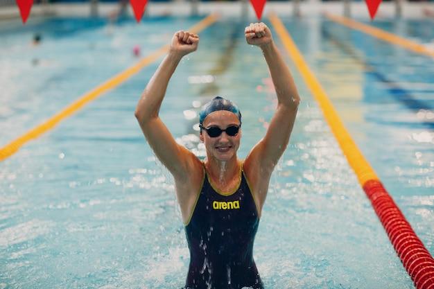 Радость портрета пловца молодой женщины радуется победе в соревнованиях по плаванию в бассейне. выиграй концепцию.