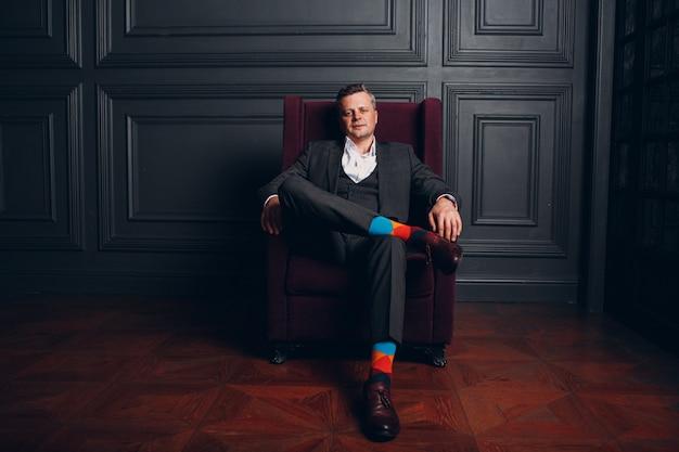 厳格なグレーのスーツとカラフルなマルチカラーソックスで座っている椅子上級ビジネスマンの肖像画。ビジネスと成功のコンセプト。