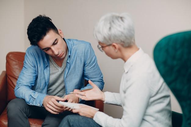 心理学者のためのレセプションの若い男性患者の相談。アドバイスのコンセプトです。