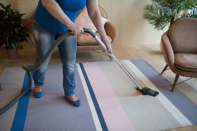 自宅のカーペットを掃除機の女性