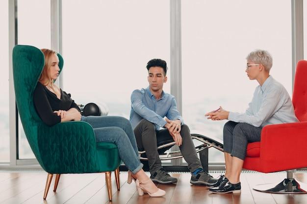 心理学者のためのレセプションでカップルの若い男性と女性患者の相談。家族の問題の概念。