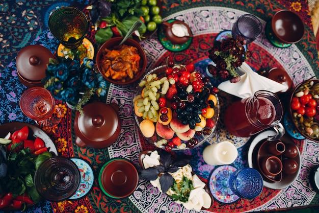 Стол с вазой с фруктами и закусками на пикник