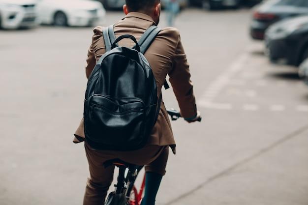 Молодой бизнесмен в костюме езда на велосипеде