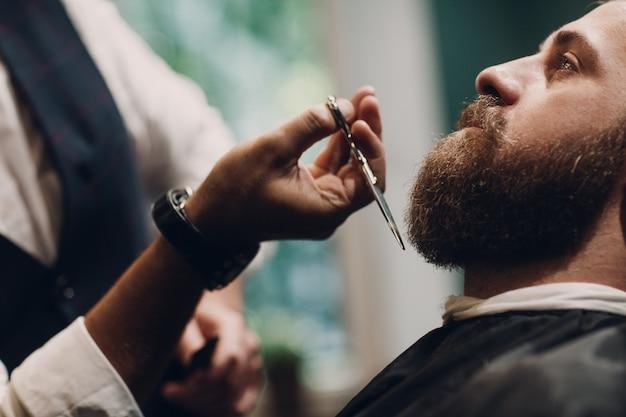 Концепция для парикмахерских. борода модель человек и парикмахер с ножницами.