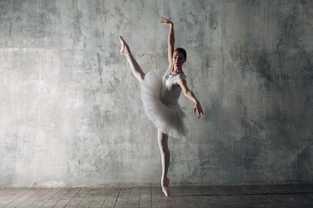バレリーナダンスの女性。プロの服、トウシューズ、白いチュチュに身を包んだ若い美しい女性バレエダンサー。