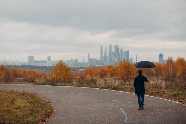 Молодой человек в черном пальто гуляя к городу под дождем с зонтиком