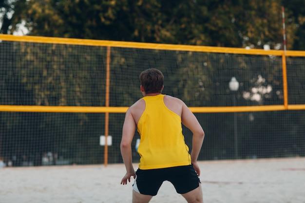 Молодые люди играют в пляжный волейбол