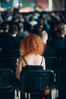 Рыжая женщина сидит на стуле вид сзади