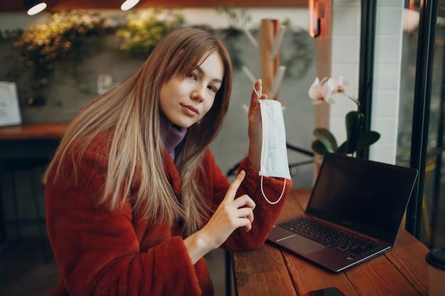Молодая женщина сидит за столом в кафе и указывая пальцем на медицинскую маску