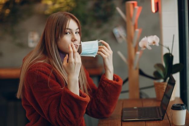 Молодая женщина сидит за столом в кафе и надевает медицинскую маску