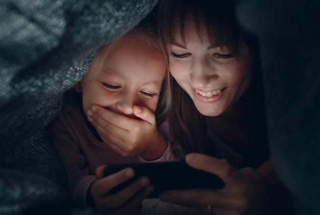 家にいる。毛布カバーの下で暗闇の中でスマートフォンでコンテンツを見て小さな娘を持つ母。