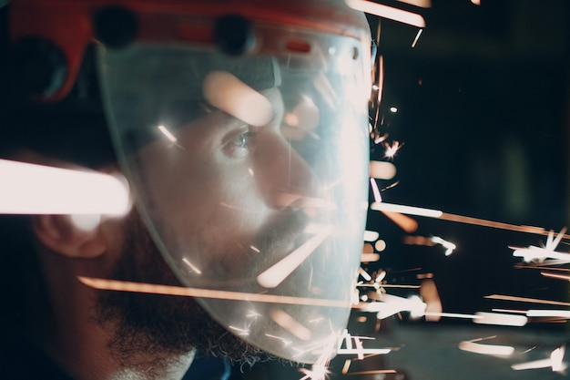 金属粒子が飛んでいる透明な防護マスクの大人のひげを生やした男が暗闇の中で火花を散らす