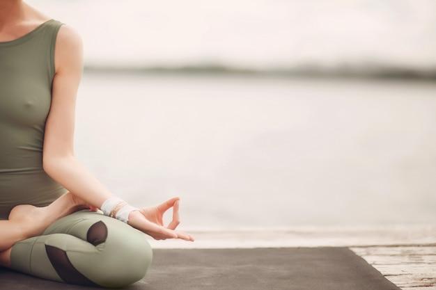 ヨガの国際デー。湖の海岸でハタヨガの練習の若い女性