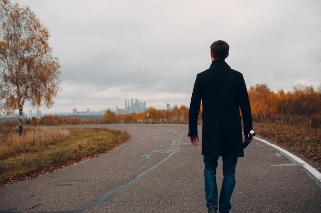 Молодой человек в черном пальто гуляя под дождем с зонтиком