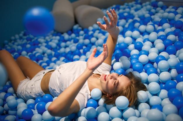 Молодая женщина играет с шариками в сухом бассейне