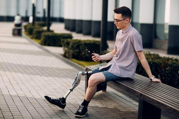 Молодой человек с протезом ноги сидит и держит мобильный телефон на улице