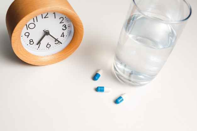 Будильник, стакан воды и белые таблетки на белом столе