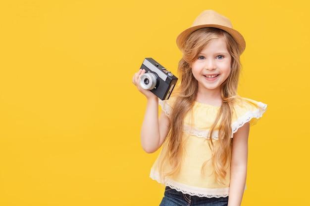 彼女の手でレトロなカメラで長い髪の幸せな少女の肖像画