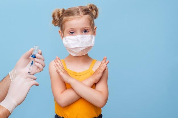 医者は医療マスクで小さなブロンドの女の子に予防接種します