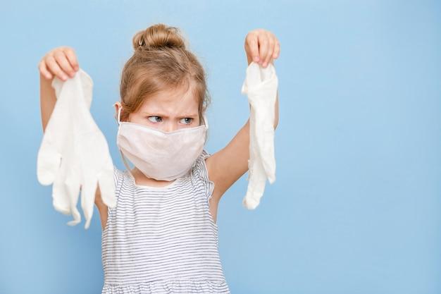 Маленькая девочка со светлыми волосами в медицинской маске держит резиновые перчатки.