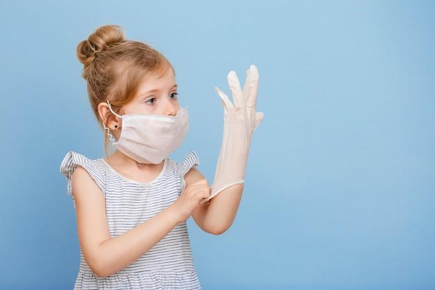 Маленькая девочка со светлыми волосами в медицинской маске носит резиновые перчатки.