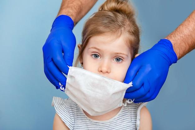 Рука доктора в синей медицинской перчатке защищает маленькую девочку от болезней и вирусов.