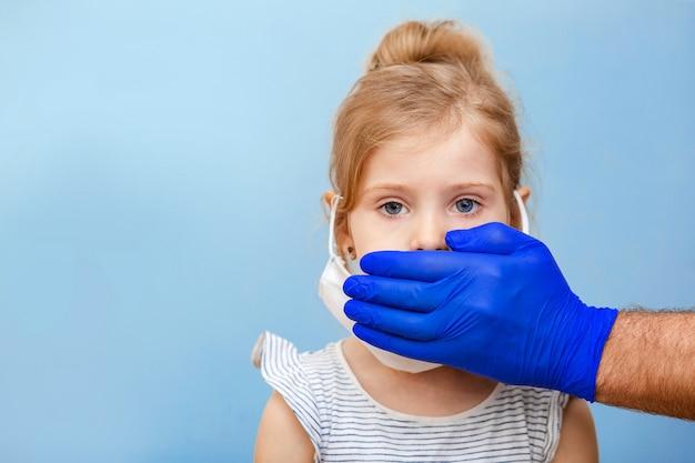 Синяя медицинская перчатка доктора защищает маленькую девочку от болезней и вирусов.