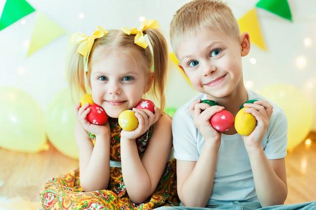 Маленькие дети, мальчик и девочка в ярких одеждах с пасхальными яйцами в руках, улыбаясь