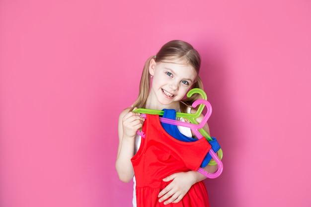 Малышка, маленькая девочка держит два платья разных цветов, радуется покупке двух по цене одного