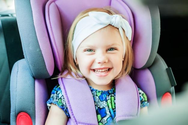 座っている小さな幸せな女の子は、赤ちゃんの車の座席に固定