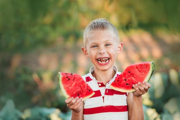 Милый смеющийся мальчик с двумя кусочками арбуза