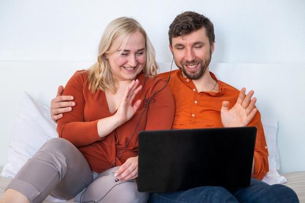 ラップトップを使用して、手を振っている若いカップル