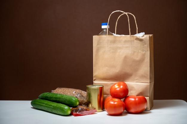 隔離された隔離期間のための食料品の危機的な食料品の入った紙袋。野菜、そば、ひまわり油、パスタ、缶詰、砂糖。フードデリバリー、寄付、コロナウイルス。