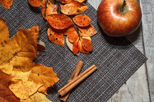 オレンジの葉の背景に熟した秋りんご