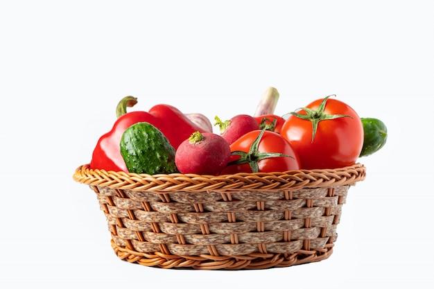 白い背景の上のバスケットに新鮮な野菜の盛り合わせ。エコ食品のコンセプト。