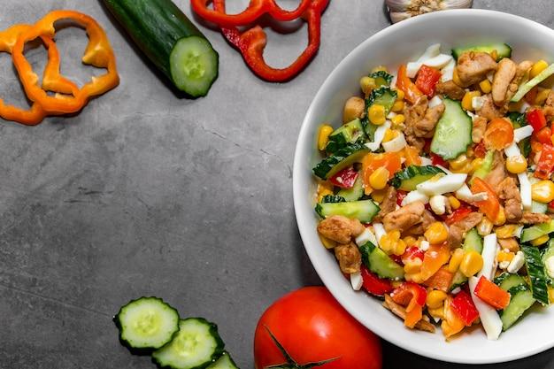 Яркий овощной салат с курицей на сером фоне бетона. делаем вкусный салат для здорового питания.