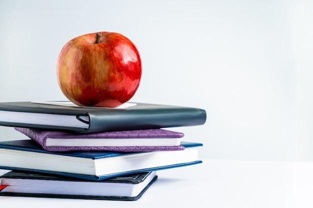 Книги и яблоко на белом фоне.