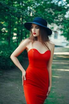 美しい女性はセクシーな赤いドレスでポーズをとってください。