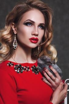 Модель молодой блондинки позирует на сером фоне с маленьким зайчиком