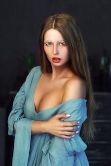 Красивая модель в голубом платье позирует в комнате