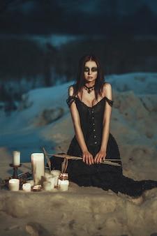 Красивая модель в черном платье позирует на снегу