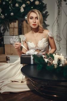 Красивая блондиночка миль позирует в рождественском украшении