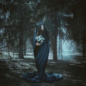 美しいモデルは青い布の森でポーズをとってください。