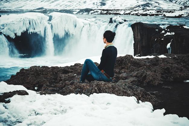 暗い髪のモデルは滝に座ってポーズをとっています