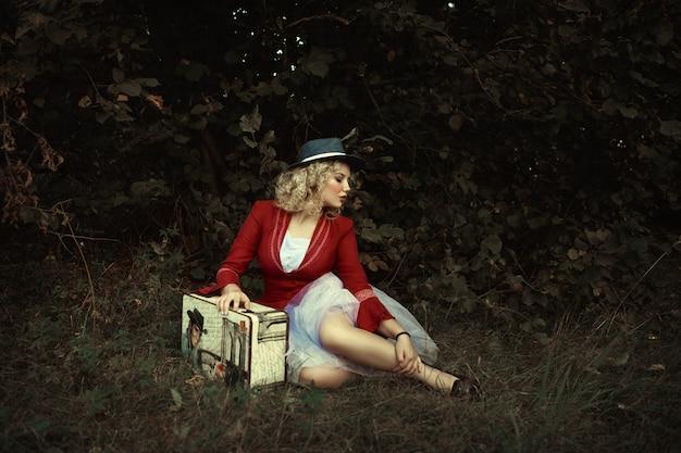 赤いジャケットの美しい少女は、明白な空気でポーズをとってください。