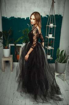 モデルは黒いドレスのインテリアスタジオでポーズをとってください。