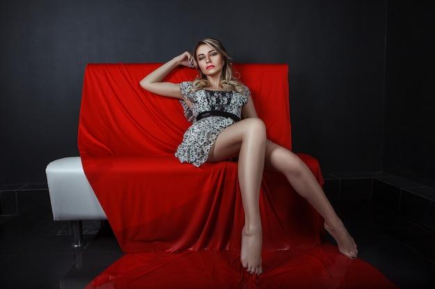 モデルは長い赤い布で暗いスタジオでポーズをとっています