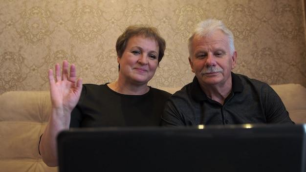 Пожилая женщина и мужчина в черном разговаривают по ноутбуку с веб-камерой с родственниками и друзьями.