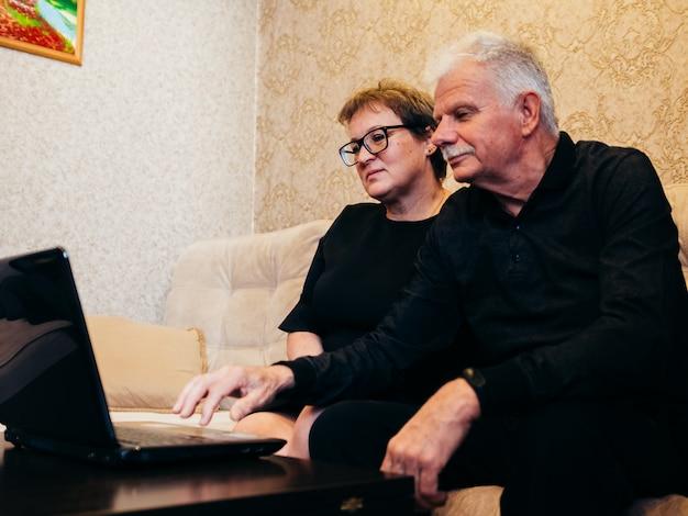 Старик и женщина в черной одежде сидят дома перед ноутбуком.
